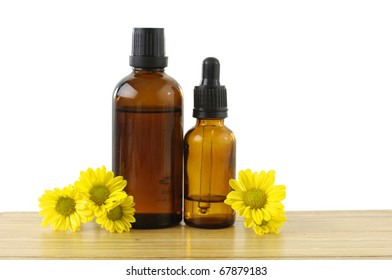 bottle of aromatic oil and yellow flower