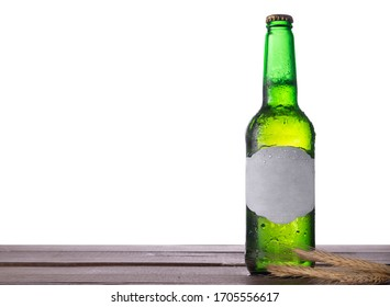 Bottle of beer, barley ears and  wheat  on a table with isolated background