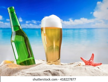 Bottle of beer with full glass in sand at beach.