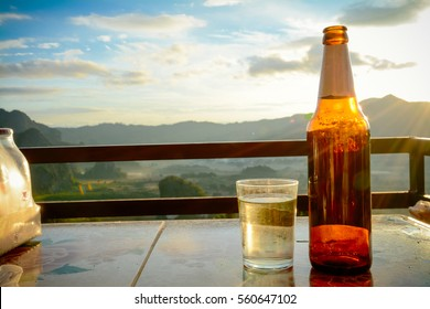 Bottle of beer and a glass ice of water on nature Background