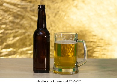 A bottle of beer and a glass mug with beer on a wooden table and yellow background