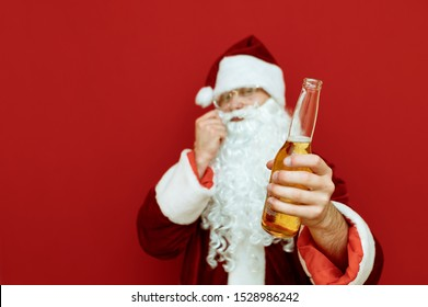 Bottle of beer in the hand of Santa Claus stands on a red background, smiling and scratching his mustache with his hand. Focus on Santa's hand with bottle of beer. Isolated. Santa Claus and alcohol