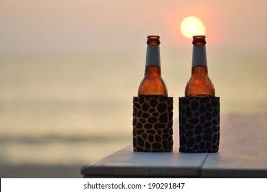 Bottle of beer on the beach at sunset