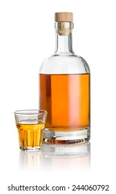 Bottle and beveled shot glass filled with amber liquid