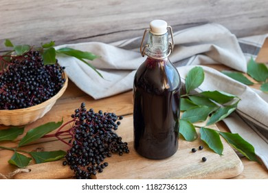 A bottle of black elder syrup with fresh berries