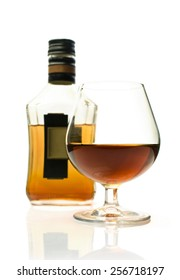 Bottle of brandy and a glass isolated on white