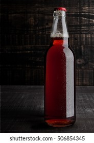 Bottle of brown ale beer with foam on wooden background