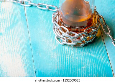 A bottle with a brown liquid around it is wound around a chain, on a wooden table