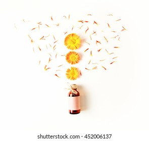 Bottle, calendula flowers and petals on a white background. The concept of a medical background. Top view, flat style.