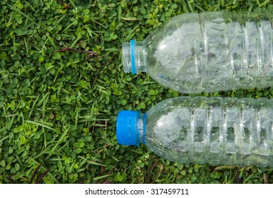 Bottle and cap water left on the grass waiting for new recyclable.