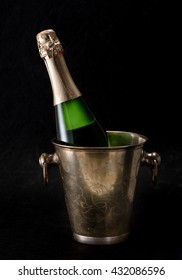 Bottle of champagne in a bucket on a black background