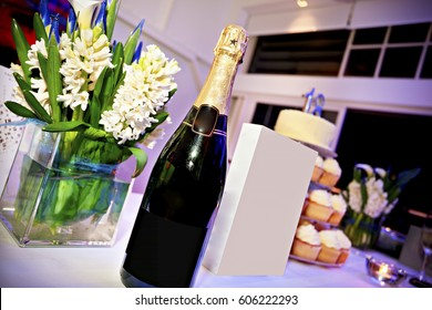 Bottle Of Champagne And Chanel Perfume Placed On Table With Glass Flower Pot Side