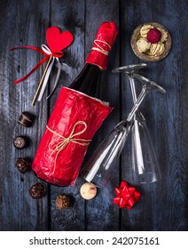 bottle of champagne, chocolate, glass and heart with ribbon on dark blue wooden background, top view