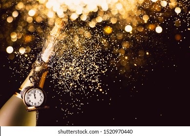 Bottle of champagne with a clock exploding with fireworks and glitter on a dark background with lights bokeh. New year party concept
