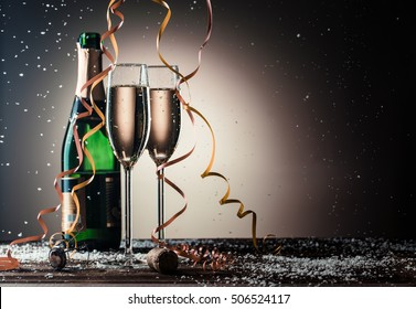 Bottle of champagne and filled glasses decorated in festive theme