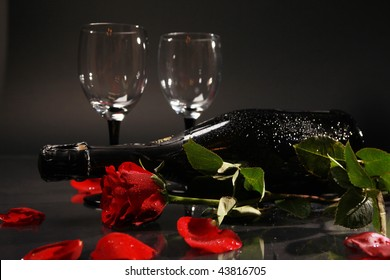 bottle of champagne glasses and red rose