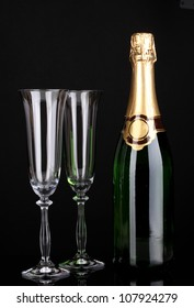 Bottle of champagne and goblets isolated on black