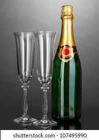 Bottle of champagne and goblets on grey background