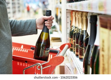 Bottle of champagne in the hands of the buyer in the store