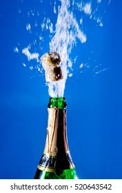 Bottle of champagne with a popping cork (against a bright blue background)