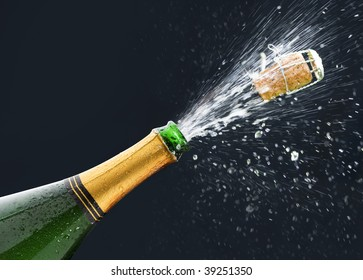 Bottle of Champagne with popping cork and Champagne spray on black background.