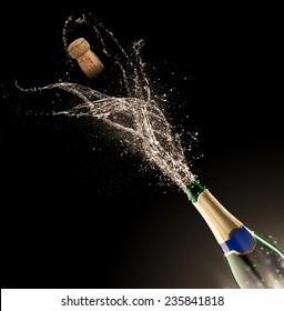 Bottle of champagne with splash isolated on black background