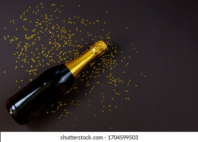 Bottle of champagne with star confetti lying on black background. New Year or anniversary celebration concept. Top view. Flat lay.