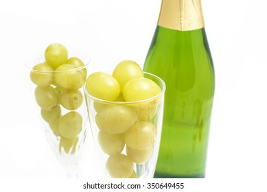 Bottle of champagne with twelve grapes of luck