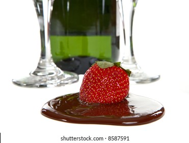 Bottle of Champagne with two flutes also a strawberry in chocolate