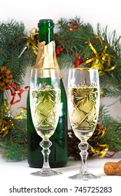 a bottle of champagne and two glasses stand on the background of a wreath of fir branches, white background, around a tinsel