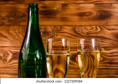 Bottle of champagne and two wineglasses on rustic wooden table