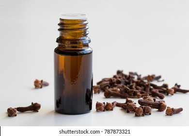 A bottle of clove essential oil with dried cloves on a white background