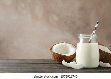 Bottle of coconut milk with straw, coconut and slice coconut on wooden background, space for text