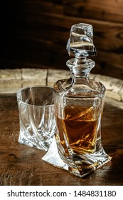 A bottle of cognac and glass on a brown wooden background. Brandy