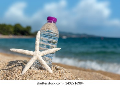 Bottle of cold fresh water with starfish on beach sand. Summer concept