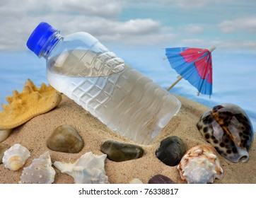 a bottle of cold water and shells on a sand