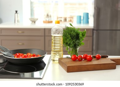 Bottle with cooking oil and ingredients on table
