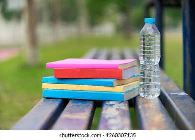 A bottle of cool fresh water placed behind the books at the park.