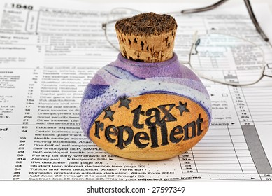 A bottle of corked tax repellent and eyeglasses on top of 1040 income tax form.