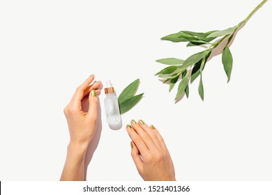 Bottle of cosmetic oil next to female hands with green manicure and fresh leaves on white background with copy space, flat lay composition.