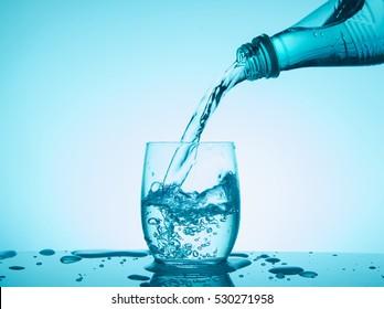 Bottle with creative splashing water on blue background.