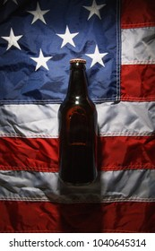 A bottle of dark beer on the American flag