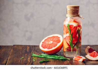 Bottle of Detox Water Infused with Sliced Raw Grapefruit and Fresh Springs of Rosemary. And Ingredients on Wooden Table. Copy Space on the Laft.