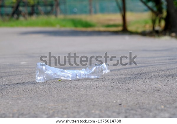 A bottle of drinking water littering on a road ground floor at the green park with blurred a trash bin in the side way for an environmental cleaning concept