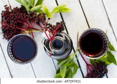 Bottle of elderberry syrup and glasses on a wooden table, top view