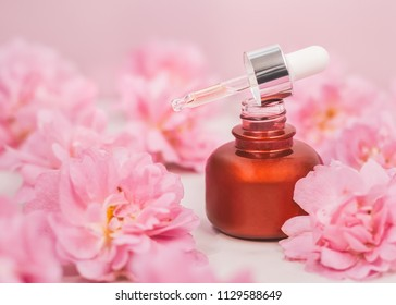 A bottle of emulsion for face care among pink rose buds.
