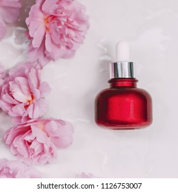 A bottle of emulsion for face care and few pink rose buds on marble background. Top view.
