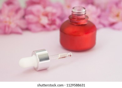 A bottle of emulsion for face care and few pink rose buds on marble background.