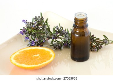 bottle of essence oil with orange slice and blossoming rosemary branch