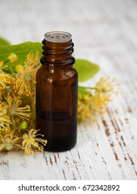bottle of essential linden oil and yellow lime flowers